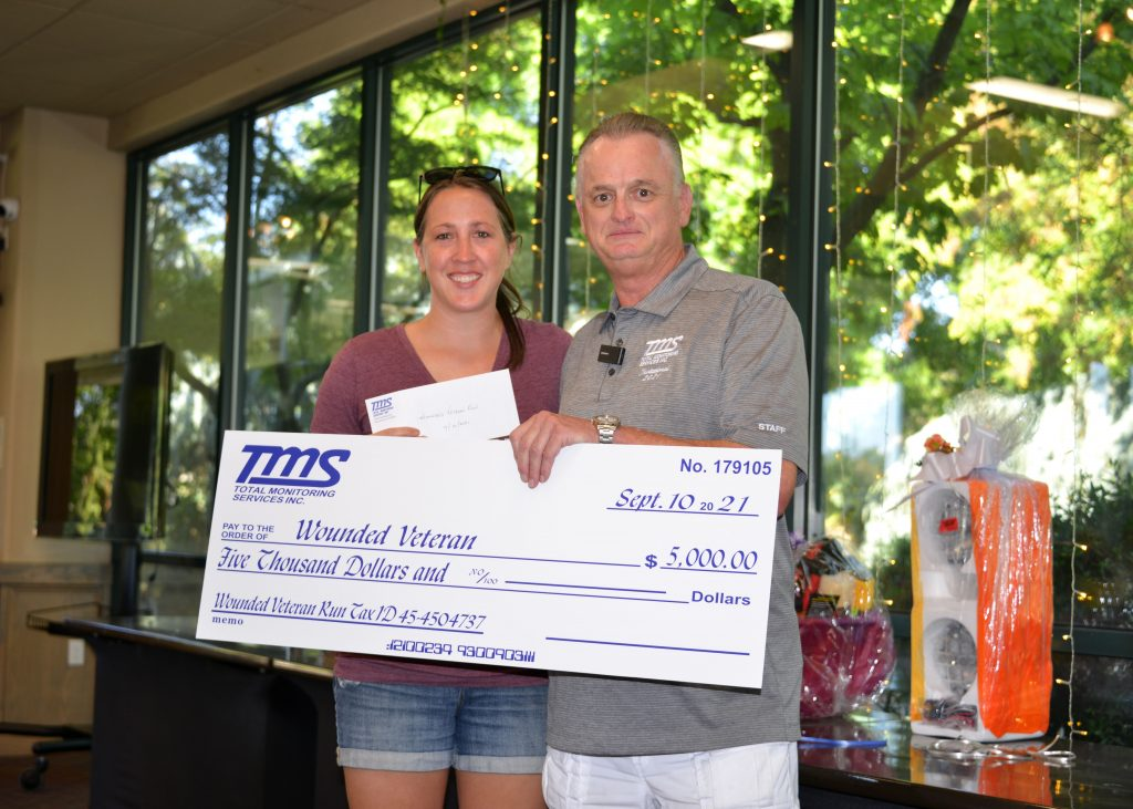 Courtney Hvostal, founder of the Wounded Veteran Run, accepts a gift of $5000 from TMS founder Timothy Sproul.